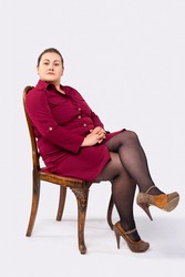 A woman is sitting on a chair. Looking smart. In a red dress an shoes. Clothes of big size. Grey background.