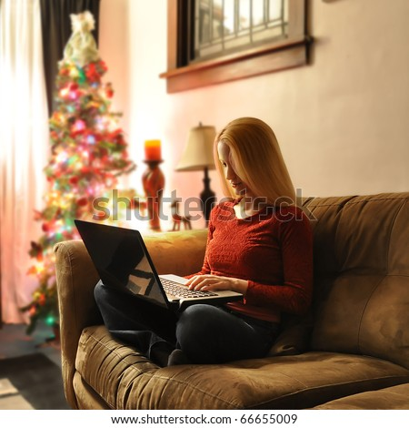 A woman is sitting on a couch shopping on her laptop computer. There is a Christmas tree in the background.