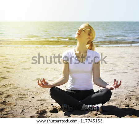 A woman is sitting on the beach with peace and tranquility. She is meditating and there is sunlight in her face.