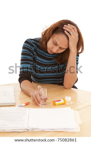A woman is sitting with pills in her hand.