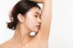 A woman is smelling her armpits.