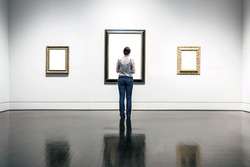 A woman is standing and looking at blank painting frames in art gallery.