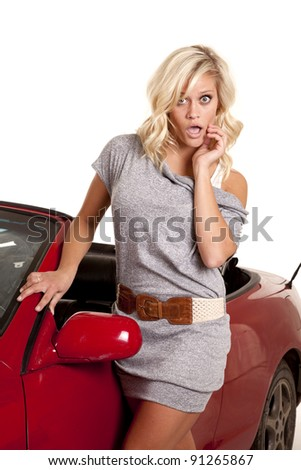 A woman is standing by her red car with a shocked expression on her face. - stock photo
