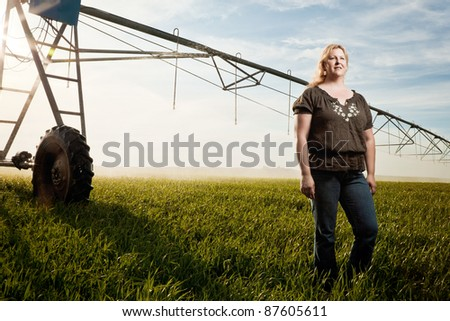 A woman is standing in a field with a pivot sprinkler behind her.