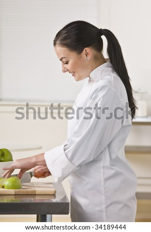 A woman is standing in a kitchen and slicing apples.  She is looking away from the camera.  Vertically framed shot.
