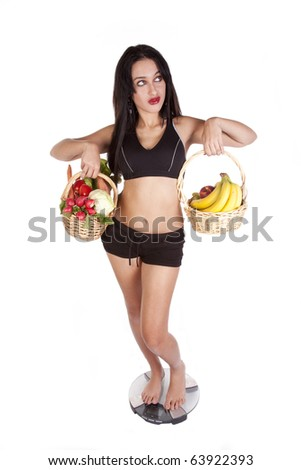 A woman is standing on the scales holding fruit and vegetables.