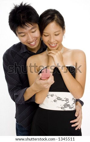 A woman is surprised by her man with a small giftbox