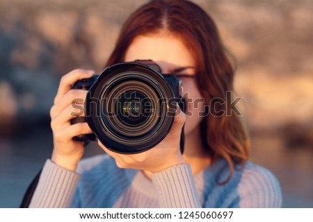 A woman is taking pictures on the background of nature