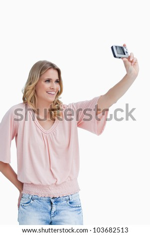 A woman is talking a photo of herself with her digital camera against a white background
