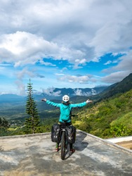 A Woman is Traveling By Bicycles in The Mountains and Enjoying the Nature Looking Towards the Horton Plains National Park   Haputale Area, Sri Lanka