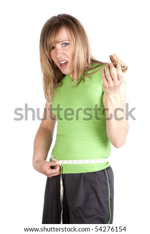 A woman is unhappy while she eats a snack and measures her waist.