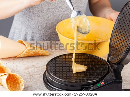 A woman is  using a non stick electrical waffle cone maker to make homemade ice cream cones. Fresh made hand rolled cones are lying on marble countertop. Mixed ingredients are mixed in yellow bowl.