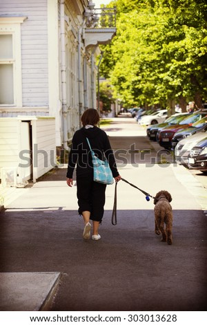 A woman is walking the dog in the streets. The dog is lagotto romagnolo also known as Italian waterdog. Image has a vintage effect applied.