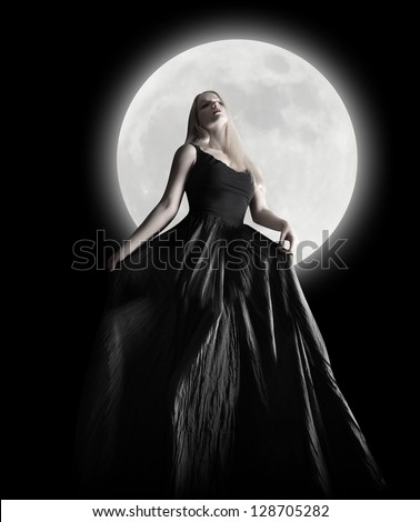 Stock Photo A woman is wearing a long black dress moving in the dark night against a full moon for a fashion or mystery concept.