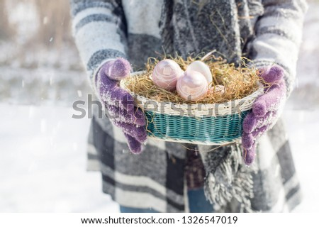 A woman is wearing an Easter nest. She wears wool clothes and wears gloves. It is snowing at Easter. Copy Space #1326547019