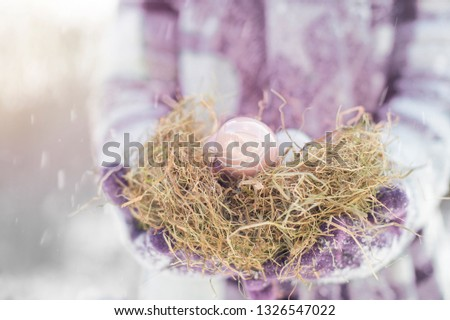 A woman is wearing an Easter nest. She wears wool clothes and wears gloves. It is snowing at Easter. Copy Space #1326547022