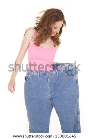A woman is wearing large pants and looking down at them.