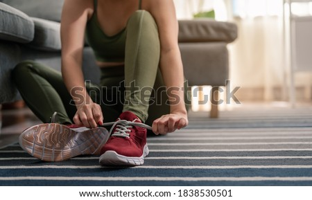 A woman is wearing shoes to exercise in her home. Exercise indoors during quarantine. Exercise, home activities