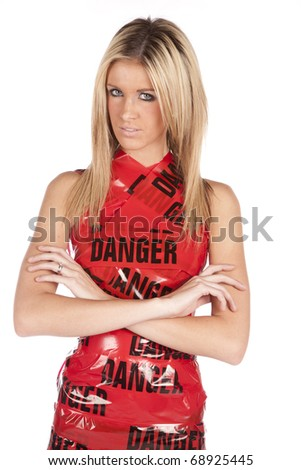A woman is wrapped in danger tape like a dress and is serious.