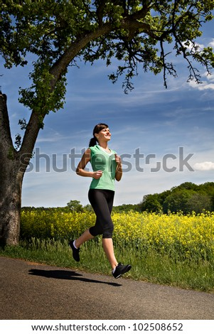 A woman jogging in front of cross country