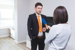 A woman journalist interviews a business man in a suit in a room with a modern interior