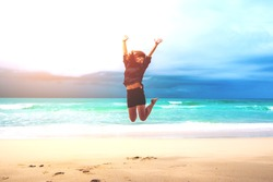A woman jumping on the beach in front of ocean with feeling happy and freedom