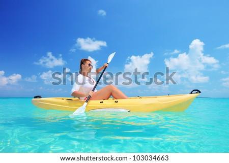 A woman kayaking on a sunny day, Kuredu island, Maldives, Lhaviyani atoll