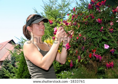A woman landscape gardener smiles as she prunes a hanging basket full of flowers.