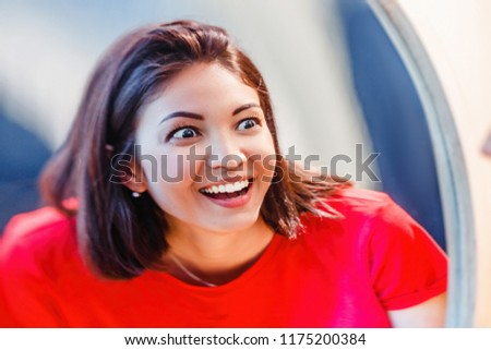 A woman laughs and looks at the reflection in a distorted mirror room