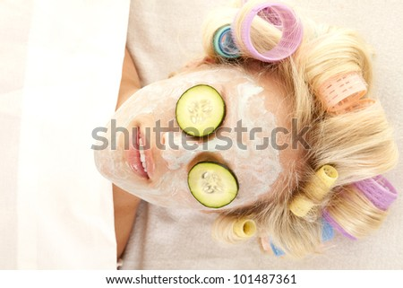 A woman laying down with curlers in her hair and a cream face mask.