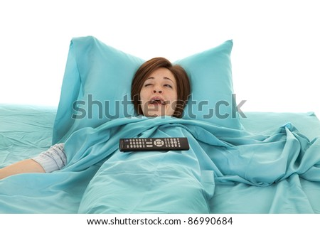 a woman laying in bed yawning and watching tv with her remote on her belly.