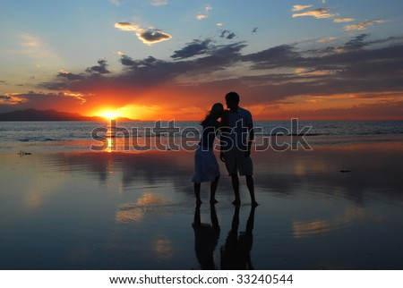 A woman leans on a man's shoulder during as they watch the sunset