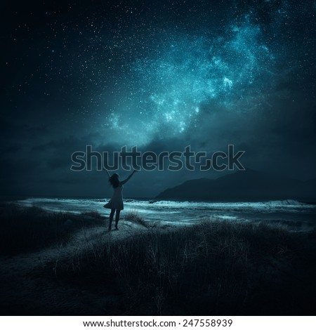 Stock Photo A woman lifting hands in praise late  at night.
