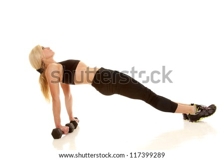 A woman lifting her back up with her hands on weights.