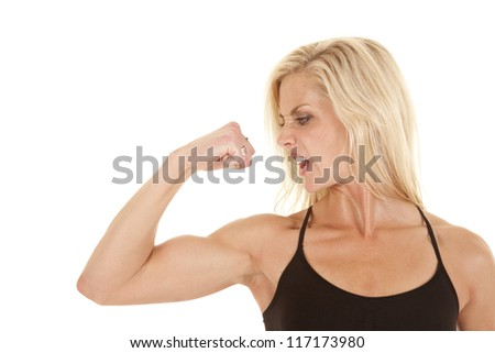 A woman looking at her arm while she is flexing with a upset expression on her face.