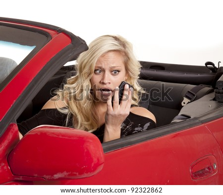 A woman looking at her cell phone with a  funny expression on her face while driving her car.