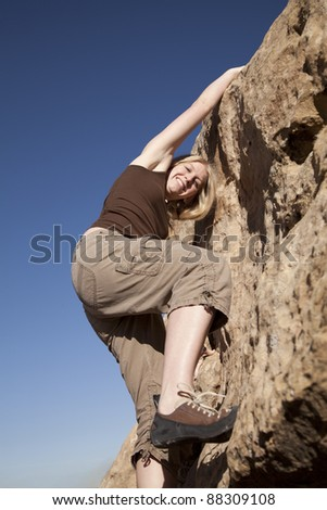 A woman looking at the camera while she is rock climbing.