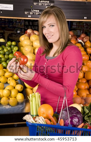 A woman looking at tomatoes and buying fruit and vegetables in a grocery store.