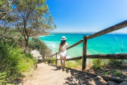 A woman looking back towards Wategoes beach at Byron Bay on Australia's east coast