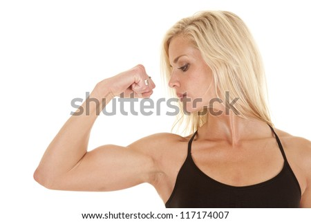 A woman looking down at her arm while she is flexing.