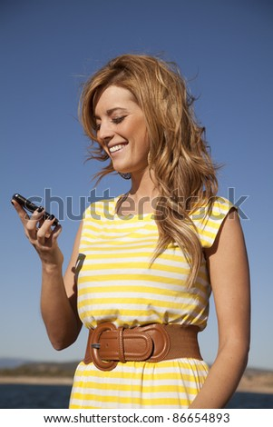 A woman looking down at her phone reading a text laughing.