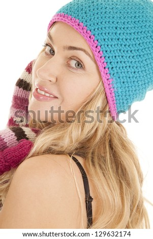 A woman looking over her shoulder with a smile on her face while wearing her hat and mittens.