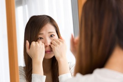A woman looks at her skin condition in a mirror.