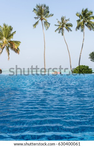 a woman lying at the infinity pool #630400061