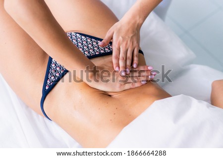 A woman making a belly massage in light procedure room. Anti-cellulite massage, diastasis. Faces are not recognizable. Stock photo ©