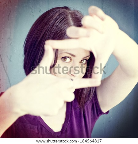 A woman making a frame with her fingers, instagram style