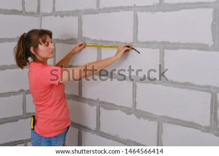 A woman measures the length of the wall in a new apartment. Distance measurements for repair work. The measuring tape to measure the space in the house was built.