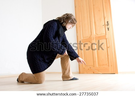 a woman measuring her floor - she has a new flat #27735037