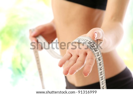 A woman measuring her waist, focus on her hand, isolated on white #91316999