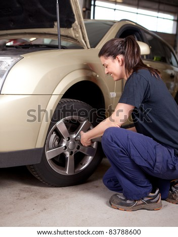 A woman mechanic loosening nuts on a wheel for a tire change